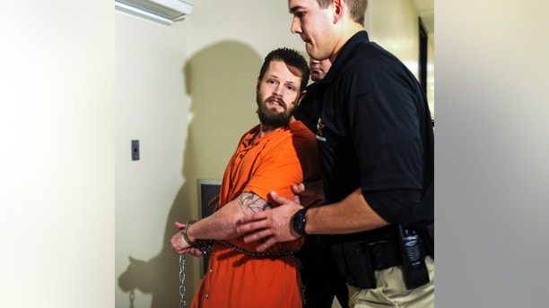 This March 19, 2015 file photo shows a police officer escorting Joseph Oberhansley through the Clark County Courthouse in Jeffersonville, Ind. A judge ruled Wednesday, Oct. 25, 2017 that Oberhansley, 36, isn't mentally competent to stand trial on charges that he killed his ex-girlfriend, 46-year-old Tammy Jo Blanton, in September 2014 and ate parts of her body. The southern Indiana judge's ruling came after she heard testimony from three doctors who evaluated him. (Tyler Stewart/News and Tribune via AP)