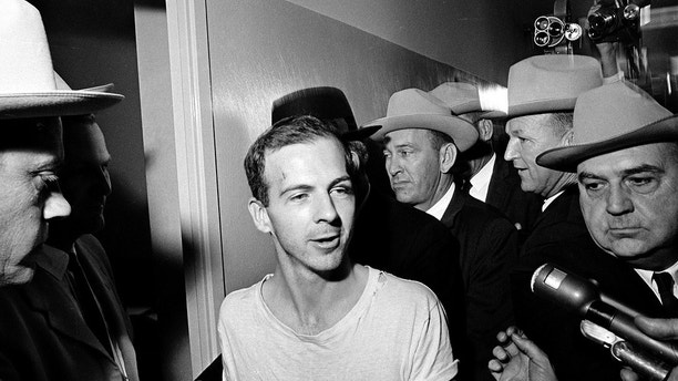 FILE - In this Nov. 23, 1963, file photo, surrounded by detectives, Lee Harvey Oswald talks to the media as he is led down a corridor of the Dallas police station for another round of questioning in connection with the assassination of U.S. President John F. Kennedy. President Donald Trump is caught in a push-pull on new details of Kennedy's assassination, jammed between students of the killing who want every scrap of information and intelligence agencies that are said to be counseling restraint.  How that plays out should be known on Oct. 26, 2017, when long-secret files are expected to be released. (AP Photo)