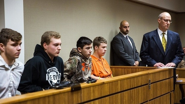 From left to right, Trevor Gray, 15, Alexzander Miller, 15, Mikadyn Payne, 16, and Kyle Anger, 17, all of Clio, Mich., appear for their arraignment in front of Judge William Crawford on Tuesday, Oct. 24, 2017, in Genesee County District Court in downtown Flint, Mich. Along with Clio resident Mark Sekelsky, 16, not pictured, the teenagers are charged with second-degree murder in a rock-throwing incident on Interstate 75. (Terray Sylvester /The Flint Journal-MLive.com via AP)