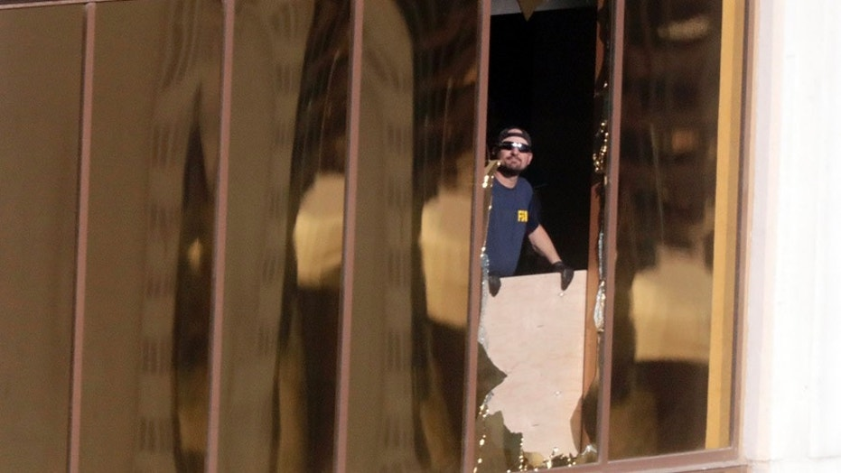 FBI agents peer out the broken window at the Mandalay Bay Hotel where a gunman opened fire on a country music concert.