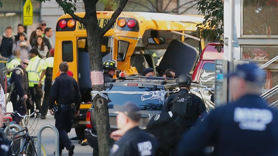 Authorities respond near a damaged school bus Tuesday, Oct. 31, 2017, in New York. A motorist drove onto a busy bicycle path near the World Trade Center memorial and struck several people on Tuesday police and witnesses said. (AP Photo/Bebeto Matthews)