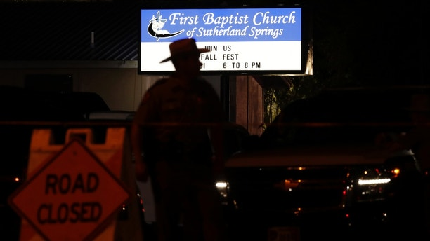 A law enforcement official stands watch outside the First Baptist Church of Sutherland Springs, the scene of a deadly shooting, Sunday, Nov. 5, 2017, in Sutherland Springs, Texas. A man dressed in black tactical-style gear and armed with an assault rifle opened fire inside the church in the small South Texas community on Sunday, killing and wounding many. The dead ranged in age from 5 to 72 years old. (AP Photo/Eric Gay)