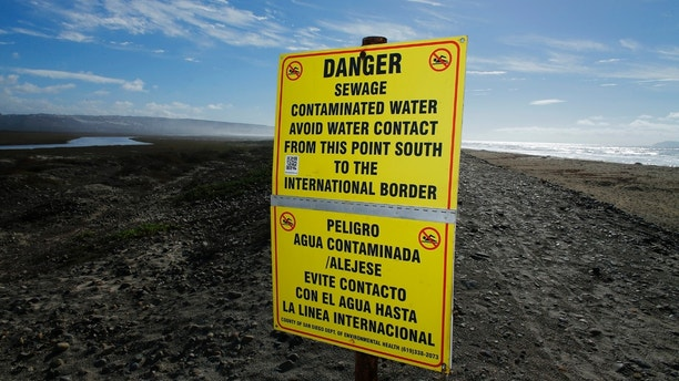 Contaminated water signs are placed along the sand following a rain storm in Imperial Beach, California December 4, 2014. A contamination alert was in effect in San Diego County Thursday along several miles of ocean shoreline just north of the U.S.-Mexico border.  The alert was issued  because of a rain-driven influx of sewage-fouled water from the Tijuana River, according to the San Diego County Department of Environmental Health.  REUTERS/Mike Blake (UNITED STATES - Tags: ENVIRONMENT SOCIETY HEALTH) - GM1EAC50G8Z01