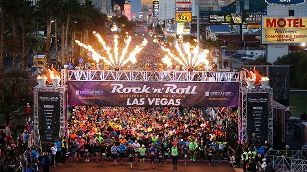 FILE - In this Nov. 16, 2014, file photo, runners begin the Rock 'n' Roll Las Vegas Marathon along the Las Vegas Strip in Las Vegas. More than 40,000 people will run on Sunday, Nov. 12, 2017, under the watchful eyes of snipers and surrounded by other law-enforcement safety measures during the Las Vegas Rock 'n' Roll Marathon, the first large-scale outdoor event the city's hosting since a gunman killed 58 people gathered at a country music festival last month. (AP Photo/John Locher, File)
