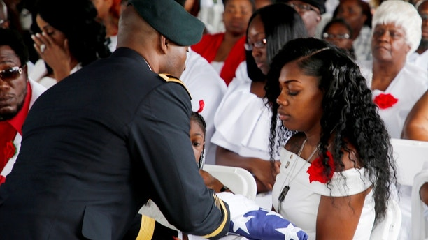 Myeshia Johnson, wife of U.S. Army Sergeant La David Johnson, who was among four special forces soldiers killed in Niger, receives the flag which draped his coffin at a graveside service in Hollywood, Florida, October 21, 2017.  REUTERS/Joe Skipper - RC1BF481DE30