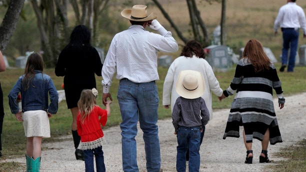 A mourner arrives with his children for the burial of Richard and Therese Rodriguez after the husband and wife were killed in the shooting at First Baptist Church of Sutherland Springs in Texas, U.S., November 11, 2017. REUTERS/Rick Wilking - RC18BFDAE6D0