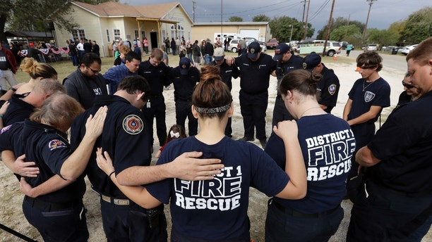 First responders join in prayer following a Veterans Day event, Saturday, Nov. 11, 2017, near the Sutherland Springs First Baptist Church, in Sutherland Springs, Texas. A man opened fire inside the church in the small South Texas community on Sunday, killing more than two dozen. (AP Photo/Eric Gay)