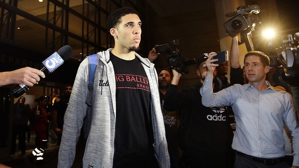 UCLA basketball player LiAngelo Ball is surrounded by reporters and photographers as he leaves Los Angeles International Airport on Tuesday, Nov. 14, 2017, in Los Angeles. Three UCLA basketball players�Ball, Jalen Hill and Cody Riley�detained in China on suspicion of shoplifting returned home, where they may be disciplined by the school as a result of the international scandal. (AP Photo/Jae C. Hong)