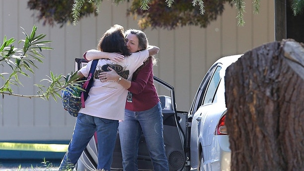 Two women embrace outside Rancho Tehama Elementary School, where a gunman opened fire Tuesday, Nov. 14, 2017, in Corning, Calif. Authorities said, a gunman choosing targets at random, opened fire in a rural Northern California town Tuesday, killing four people at several sites and wounding others at the elementary school before police shot him dead. (AP Photo/Rich Pedroncelli)