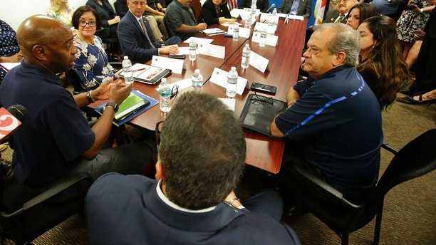 Senior FEMA officer Willie G. Nunn, left, talks about relief efforts for Puerto Ricans coming to Florida with Gov. Rick Scott, back center, and local Central Florida leaders during a roundtable discussion, Monday, Nov. 13, 2017, in Kissimmee, Fla. (AP Photo/John Raoux)