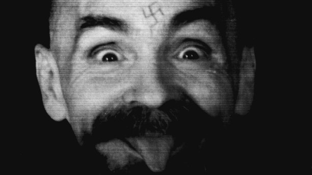 - PHOTO TAKEN 25AUG1989 - Charles Manson clowns around as he is led to his cell upon the conclusion of his exclusive interview with Reuters August 25, 1989. - PBEAHUNZPAU