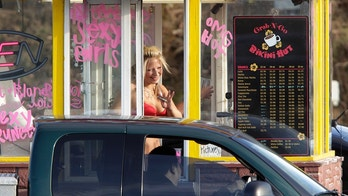 "A barista at a Grab-N-Go Bikini Hut espresso stand holds money as she waves to a customer, Tuesday, Feb. 2, 2010, just outside the city limits of Everett, Wash., in Snohomish County. Coffee shops in the Seattle area introduced the world to ""bikini baristas"" three years ago, but now Snohomish County and other areas are tightening their rules for the stands, such as requiring employees to wear at least the equivalent of a bikini or face regulation under adult entertainment ordinances. (AP Photo/Ted S. Warren)"