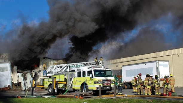 Firefighters work at the scene of of a fire Monday, Nov. 20, 2017, at the Verla International cosmetics factory on Temple Hill Road in New Windsor, N.Y. Authorities say two explosions and a fire at the cosmetics factory in the Hudson Valley have left numerous people injured, including firefighters caught in the second blast. (Jerry Barao via AP)