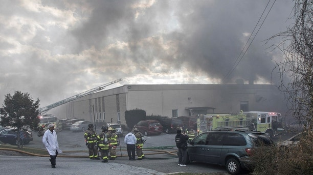 Firefighters remain on the scene of a fire at the Verla International cosmetics factory on Monday, Nov. 20, 2017, in New Windsor, N.Y.  Authorities say two explosions and a fire at the cosmetics factory in the Hudson Valley have left numerous people injured, including firefighters caught in the second blast.  (Allyse Pulliam/Times Herald-Record via AP)