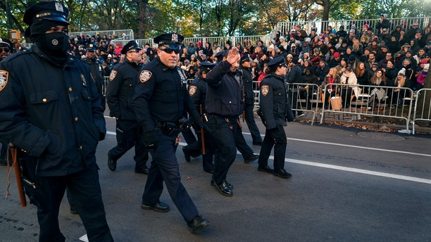 New York Police Department officers are greeted by people before the start of the Macy's Thanksgiving Day Parade in New York, Thursday, Nov. 23, 2017. (AP Photo/Craig Ruttle)
