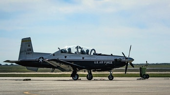 An L3 Communications crew chief leads a T-6 Texan II crew to the active runway at Vance Air Force Base, Oklahoma, Oct. 19. Since 1960, Vance Airmen have partnered with civilian contractors to train tomorrow's military aviators. (U.S. Air Force photo by David Poe)