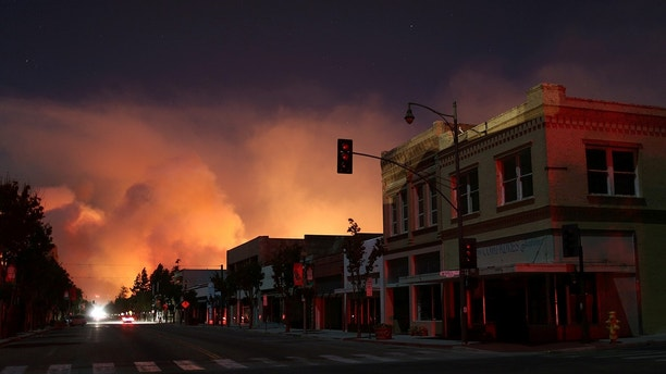 Downtown is darkened by a power outage with smoke rising in the distance as strong winds push the Thomas Fire across thousands of acres in Santa Paula, California, U.S., December 5, 2017.      REUTERS/David McNew - RC1B63D603D0