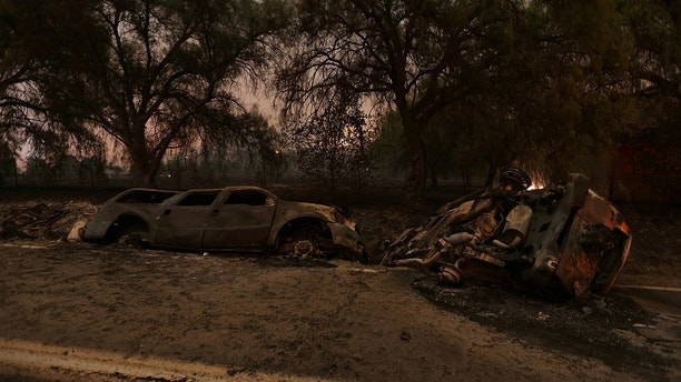 The burned remains of crashed cars are seen at night on a country road as strong winds push the Thomas Fire across thousands of acres near Santa Paula, California, U.S., December 5, 2017.      REUTERS/David McNew - RC130B5E1270