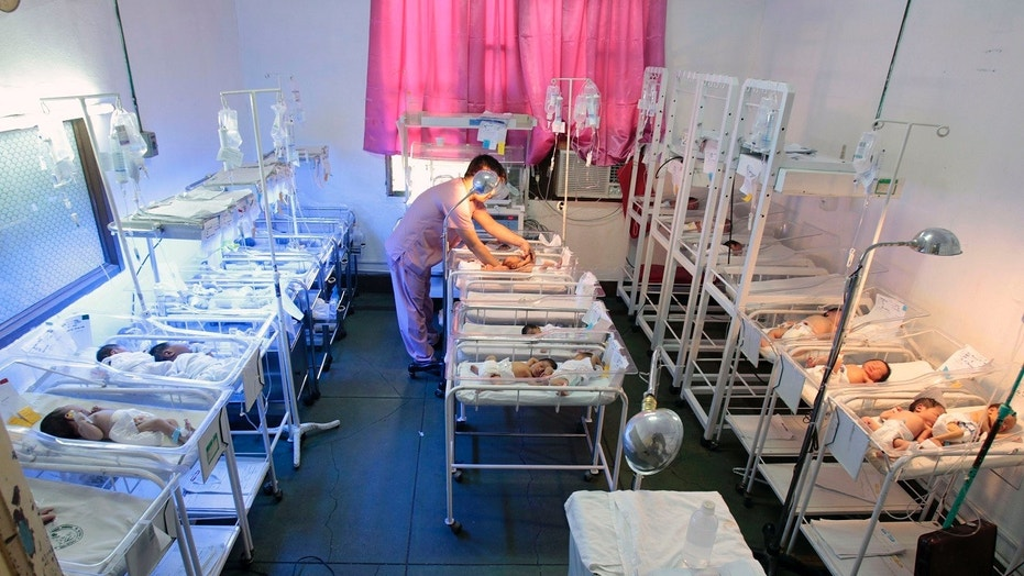 A nurse takes care of a newly born baby inside a nursery station at a hospital in Manila, Oct. 1, 2010.