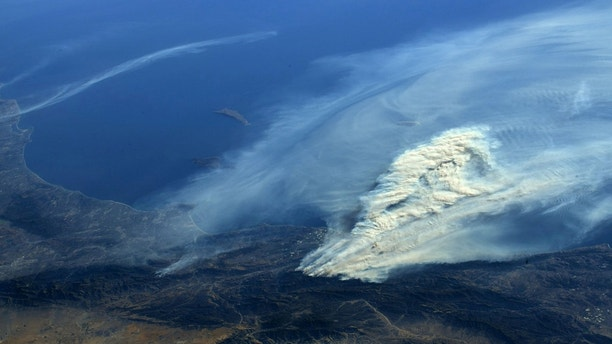 A photo taken from the International Space Station and moved on social media by astronaut Randy Bresnik shows smoke rising from wildfire burning in Southern California, U.S., December 6, 2017.  Courtesy @AstroKomrade/NASA/Handout via REUTERS   ATTENTION EDITORS - THIS IMAGE HAS BEEN SUPPLIED BY A THIRD PARTY. - RC1322C80A30