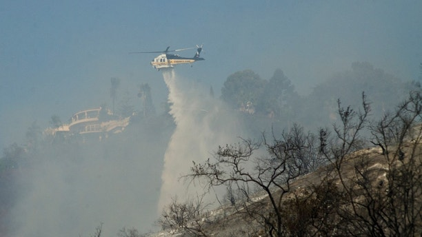 A helicopter drops water on hotspots left by the Skirball fire near the Bel Air neighborhood on the west side of Los Angeles, California, U.S., December 6, 2017.      REUTERS/Andrew Cullen - RC1D5BC8ED80
