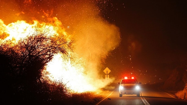 Fire personnel drive along West Lilac Road as the Lilac Fire burns near Bonsall, Calif., Thursday, Dec. 7. 2017. (K.C. Alfred/The San Diego Union-Tribune via AP)