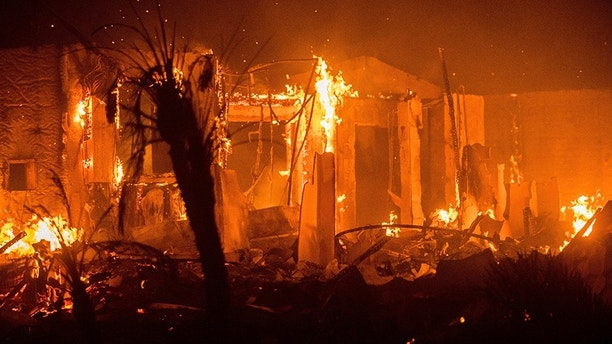 Flames consume a structure as the Lilac fire burns in Bonsai, Calif., on Friday, Dec. 8, 2017. The blaze burned numerous structures and thousands of acres according to fire officials. Wind-swept blazes have forced tens of thousands of evacuations and destroyed dozens of homes in Southern California. (AP Photo/Noah Berger)
