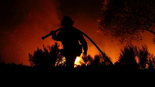 A firefighter works at the top of a hill as the Lilac Fire, a fast moving wild fire, burns through Bonsall, California, U.S., December 7, 2017.      REUTERS/Mike Blake - RC1B0E6D4310