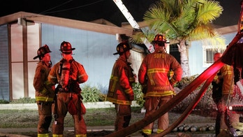 Firefighters stand in front of the house where a small plane crashed into it in San Diego, Saturday, Dec. 9, 2017. Authorities in southern California say at least two people are dead after a single-engine, six-seat Beech BE36 Bonanza crashed into a home. The plane had taken off from Montgomery Field about a half mile away. (Hayne Palmour IV/The San Diego Union-Tribune via AP)