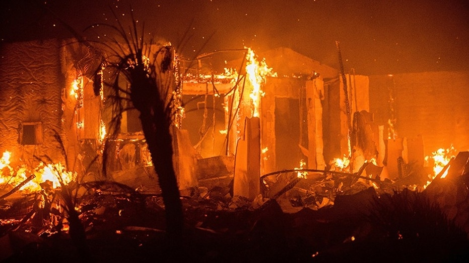 Flames consume a structure as the Lilac fire burns in Bonsall, Calif.