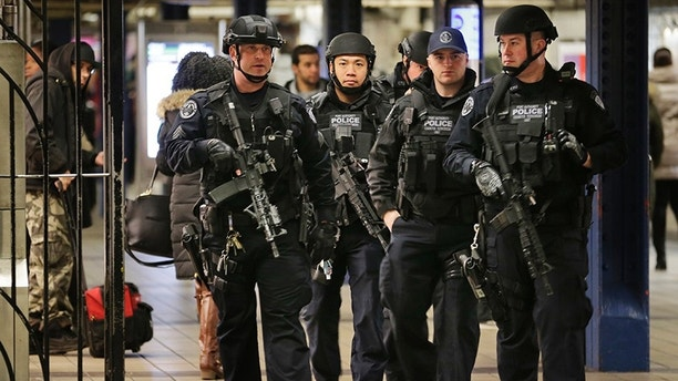 Police officers patrol in the passageway connecting New York City's Port Authority bus terminal and the Times Square subway station on Tuesday, Dec. 12, 2017, near the site of Monday's explosion. Commuters returning to New York City's subway system on Tuesday were met with heightened security a day after a would-be suicide bomber's rush-hour blast in the heart of the New York City subway system failed to cause the bloodshed he intended. (AP Photo/Seth Wenig)