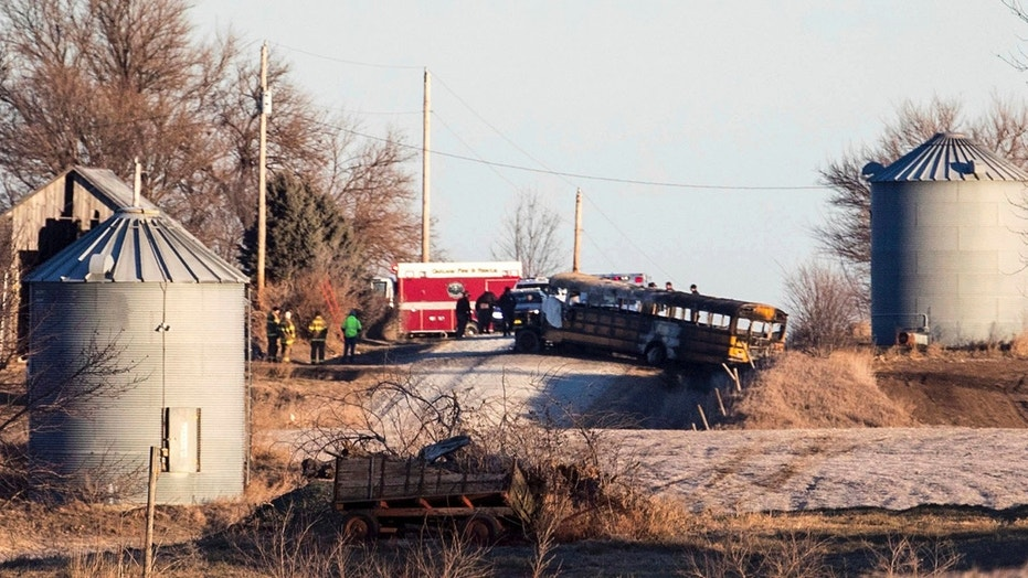 Investigators work the scene of a school bus fire that killed two people on Dec. 12.