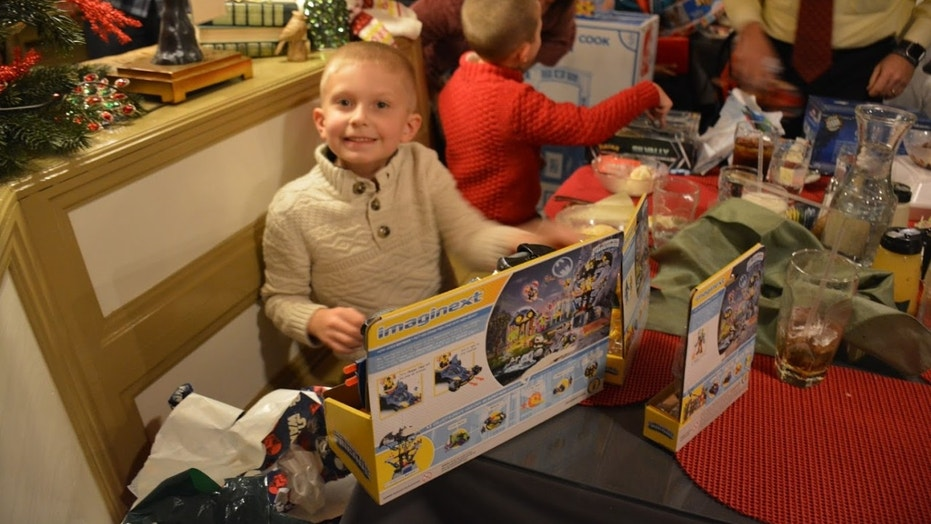 A child opens his holiday gifts at the event, which was organized by the Wounded Warrior Project Pfizer Pharmaceuticals.