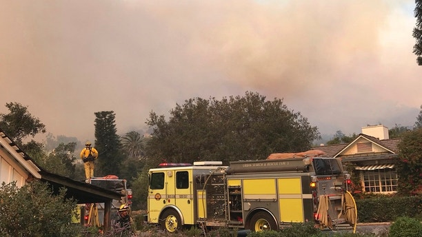 In this photo provided by the Santa Barbara County Fire Department,fire engines provide structure protection at the historic San Ysidro Ranch in Montecito, Calif., Saturday, Dec. 16, 2017. Santa Barbara County has issued new evacuation orders as a huge wildfire bears down on Montecito and other communities. The Office of Emergency Services announced the orders Saturday as Santa Ana winds pushed the fire close to the community.  Mike Eliason/Santa Barbara County Fire Department via AP)