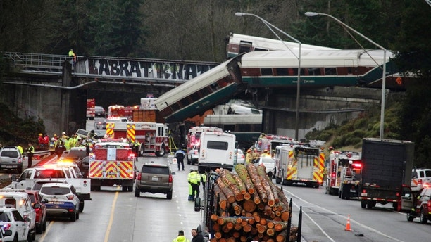 "A derailed train is seen on southbound Interstate 5 on Monday, Dec. 18, 2017, in DuPont, Wash. An Amtrak train making an inaugural run on a new route derailed south of Seattle on Monday, spilling train cars onto a busy interstate in an accident that resulted in ""multiple fatalities"" and numerous injuries, authorities said.  (AP Photo/Rachel La Corte)"