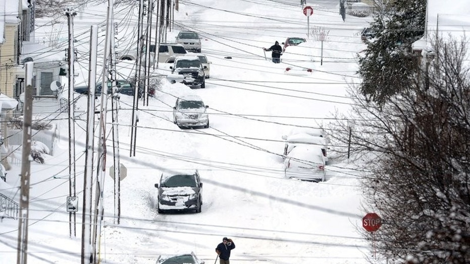 Erie, Pa., residents dig out on Tuesday, Dec. 26, 2017, after an unprecedented two-day snowfall. The National Weather Service office in Cleveland says the storm brough 34 inches on Christmas Day, a new all-time daily snowfall record for Erie.