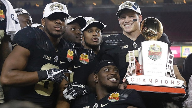 Purdue quarterback Elijah Sindelar, top right, holds the trophy next to teammates after their 38-35 win over Arizona during the Foster Farms Bowl NCAA college football game Wednesday, Dec. 27, 2017, in Santa Clara, Calif. (AP Photo/Marcio Jose Sanchez)