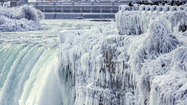 Visitors take photographs at the brink of the Horseshoe Falls in Niagara Falls, Ontario, as cold weather continues through much of the province on Friday, Dec. 29, 2017. (Aaron Lynett/The Canadian Press via AP)
