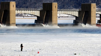 A person fishes near Lock and Dam No. 11 in Dubuque, Iowa, on Monday, Jan. 1, 2018. The area is seeing bitterly cold temperatures to start the new year. (Nicki Kohl/Telegraph Herald via AP)