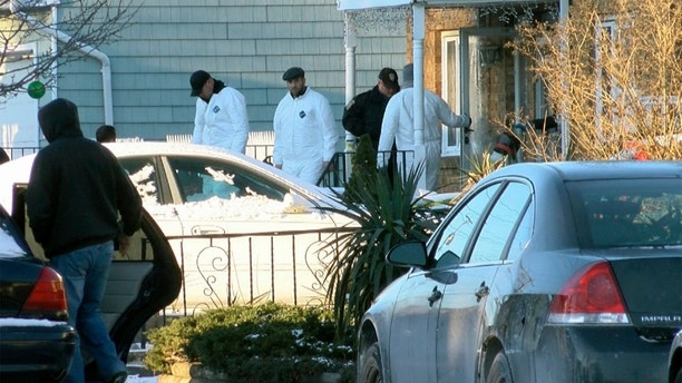 Authorities investigate outside a home in Long Branch, N.J., Monday, Jan. 1, 2018. A 16-year-old has been arrested after his parents, sister and a family friend were found dead inside the home where they lived, authorities said Monday. (Thomas P. Costell/The Asbury Park Press via AP)