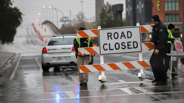Two Savannah Chatham Metro Police officers set up a barricade in front of a bridge that was closed due to ice on the road, Wednesday, Jan. 3, 2018, in Savannah, Ga. A brutal winter storm scattered a wintry mix of snow, sleet and freezing rain from normally balmy Florida up the Southeast seaboard Wednesday. (AP Photo/Stephen B. Morton)
