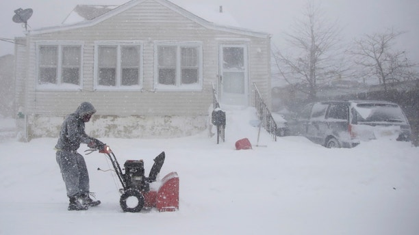 Gilberto Colin gets a head start on snowplowing his property during the middle of a snowstorm, Thursday, Jan. 4, 2018, in Neptune, N.J. A massive winter storm swept from the Carolinas to Maine on Thursday, dumping snow along the coast and bringing strong winds that will usher in possible record-breaking cold. (AP Photo/Julio Cortez)
