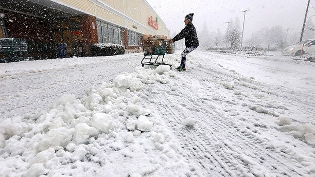 A woman fights to drag her shopping cart to her vehicle after exiting the Shaws Supermarket in Dartmouth, Mass., as a snowstorm sweeps across the area, Thursday, Jan. 4, 2018. (Peter Pereira/Standard Times via AP)