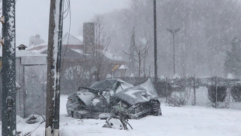 An elderly couple were rescued by two bystanders after their car got stuck in snow on a rail crossing.