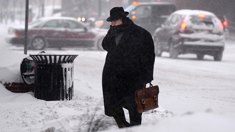 A man crosses street in downtown Syracuse, N.Y., Friday. Frigid temperatures, some that felt as cold as minus 30 degrees, moved across the East Coast on Friday as the region dug out from a massive winter storm.