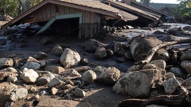 A damaged car sits over fallen and debris behind downed power lines in Montecito, Calif., Wednesday, Jan. 10, 2018. Dozens of homes were swept away or heavily damaged and several people were killed Tuesday, as downpours sent mud and boulders roaring down hills stripped of vegetation by a gigantic wildfire that raged in Southern California last month. (AP Photo/Marcio Jose Sanchez)