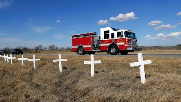 Ryland Ward, who was shot during a Nov. 5 church shooting, looks out the passenger window as he passes a memorial of crosses as he returns home after his release from the hospital while riding in the cab of a firetruck, Thursday, Jan. 11, 2018, in Sutherland Springs, Texas. Ward, 6, was shot several times and was the last victim still hospitalized following the church massacre in South Texas. (AP Photo/Eric Gay)