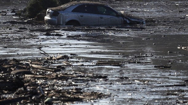 A car sits in flooded water in Montecito, Calif., Thursday, Jan. 11, 2018. Rescue workers slogged through knee-deep ooze and used long poles to probe for bodies Thursday as the search dragged on for victims of Tuesday's storm after mudslides slammed this wealthy coastal town. (AP Photo/Marcio Jose Sanchez)
