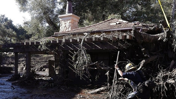 Alex Broumand of the Montecito Fire Department walks in mud in front of homes damaged from storms in Montecito, Calif., Thursday, Jan. 11, 2018. Rescue workers slogged through knee-deep ooze and used long poles to probe for bodies Thursday as the search dragged on for victims of the mudslides that slammed this wealthy coastal town. (AP Photo/Marcio Jose Sanchez)