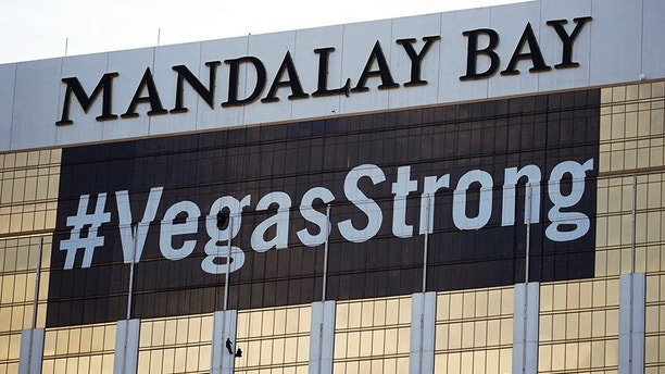 "FILE - In this Oct. 16, 2017, file photo, workers install a #VegasStrong banner on the Mandalay Bay hotel and casino in Las Vegas. The official slogan of Las Vegas, ""What happens here, stays here,"" is back by popular demand. The destination's tourism agency revived the 15-year-old slogan this week, three months after it was put on hold following the October mass shooting. Stephen Paddock opened fire from the hotel on an outdoor country music concert, killing 58 and injuring hundreds. (AP Photo/John Locher, File)"